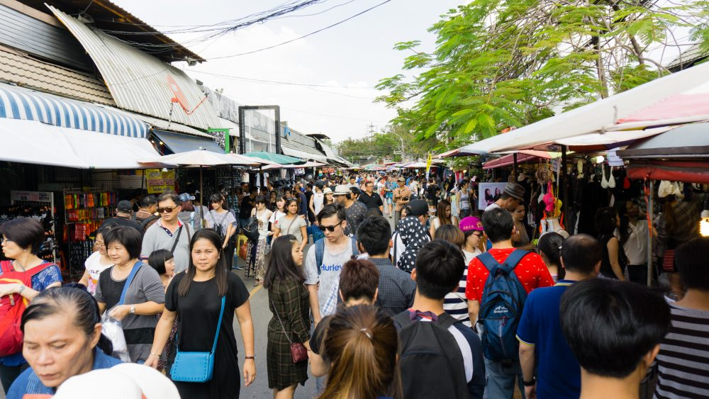 Tourists and locals in a crowded main walkway at Chatuchak Market