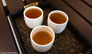 Three cups of hot tea on a tray
